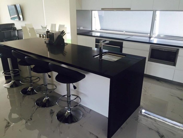 black-island-top-in-kitchen-with-stools-700x526